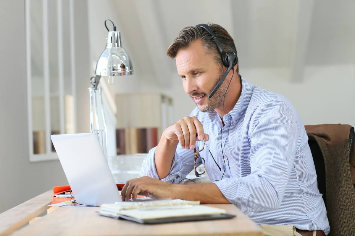 A man working from home using a laptop and a headset