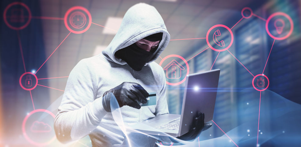 Masked and hooded man holding credit card and a laptop