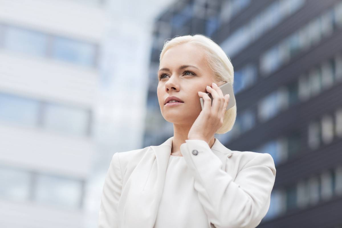 Blonde businesswoman in a white suit talking on her cellphone