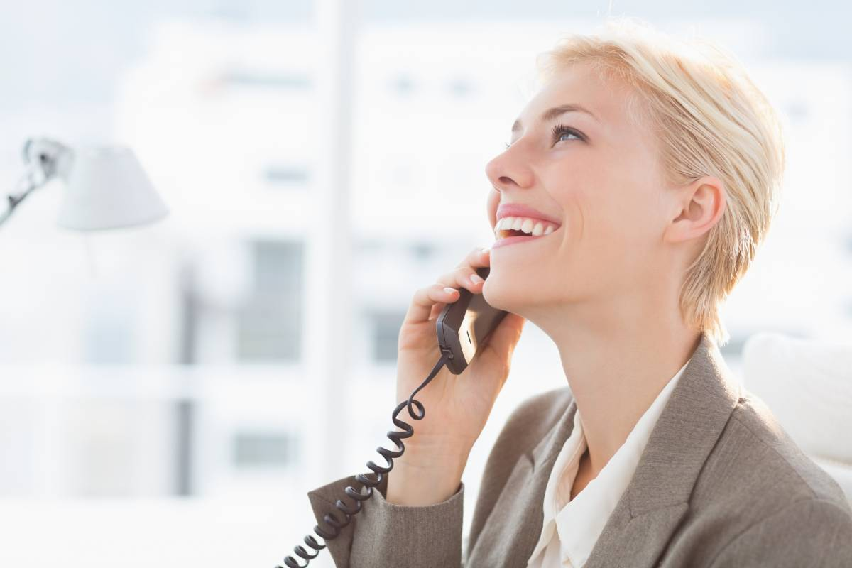 Woman with short blond hair talking and smiling while on the phone