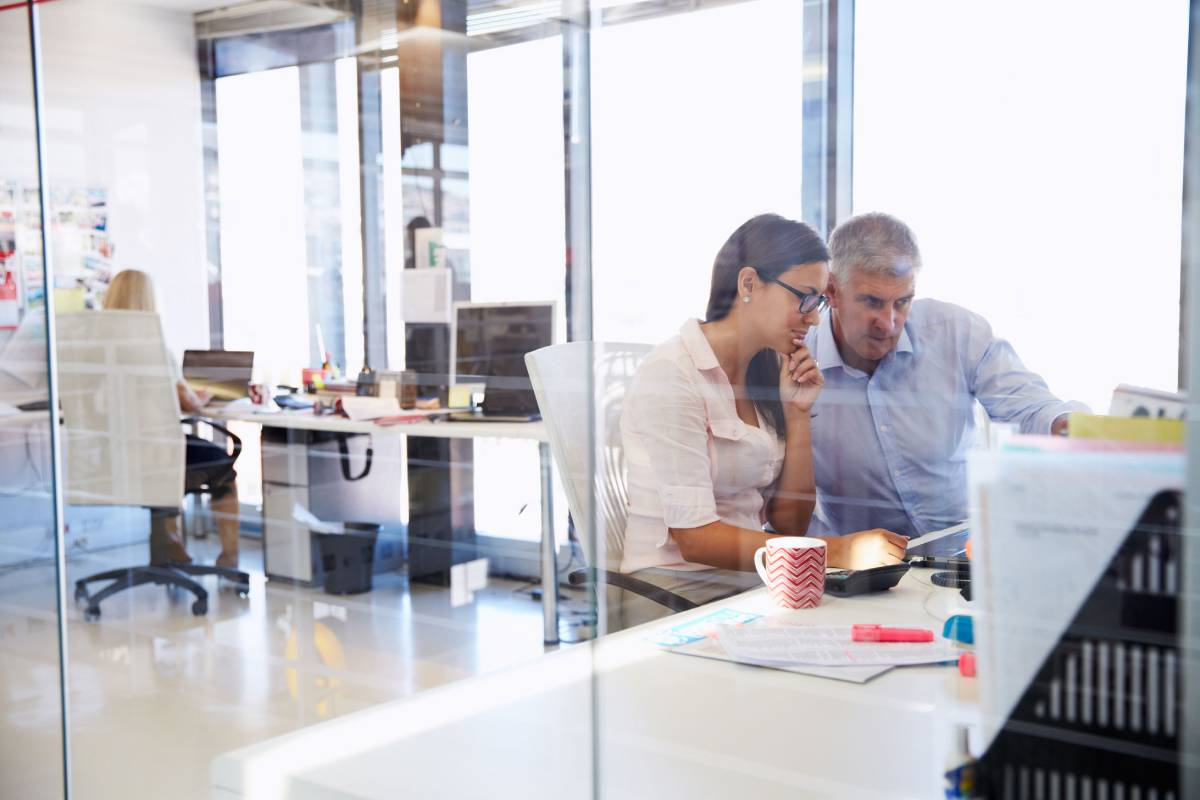 Man and woman sitting at a desk looking at a desktop computer